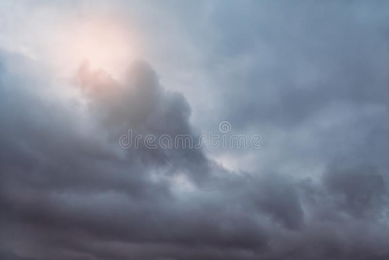 Solljussken till och med en grå åskmoln arkivbilder