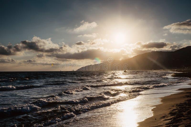 Solljussolnedgången på horisonthavet på bakgrundsseascapeatmosfär rays soluppgång Koppla av siktsvåghavet med kitesurfing på sand arkivfoton