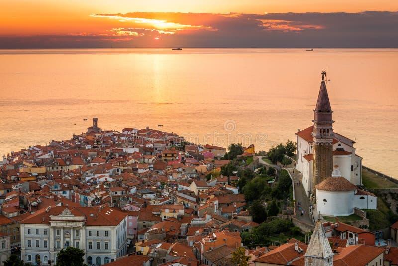 Solnedgång över Adriatiskt havet och gammal stad av Piran, Slovenien arkivfoton