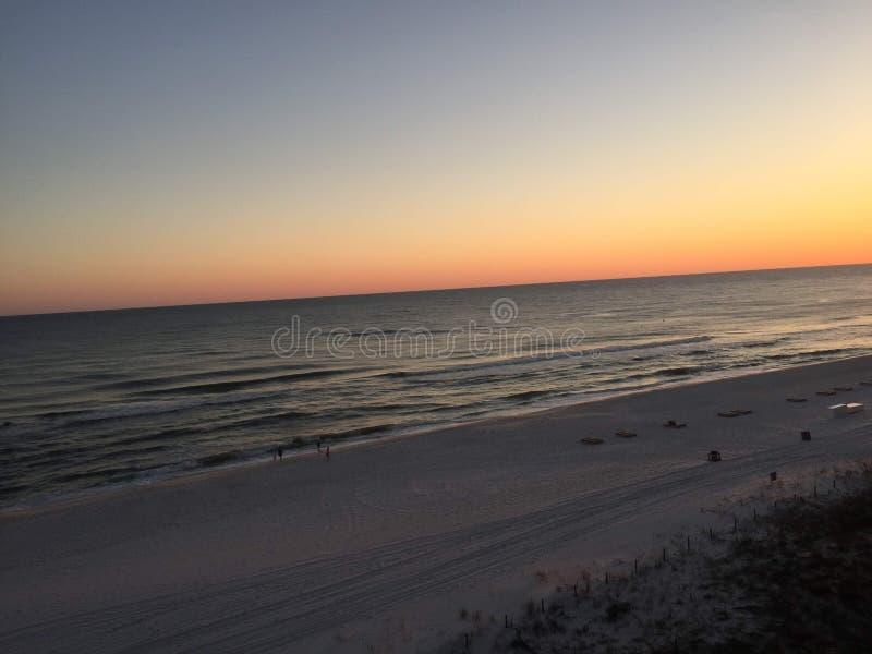 Solnedgång över Atlanticet Ocean med vågor som sköljas upp på stranden långsamt på en sandig strand royaltyfri foto