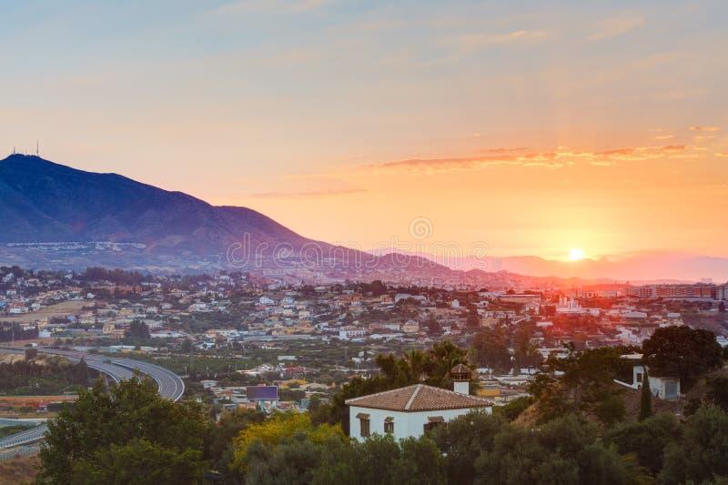 Solnedgång över berg och staden Mijas, Spanien royaltyfria foton