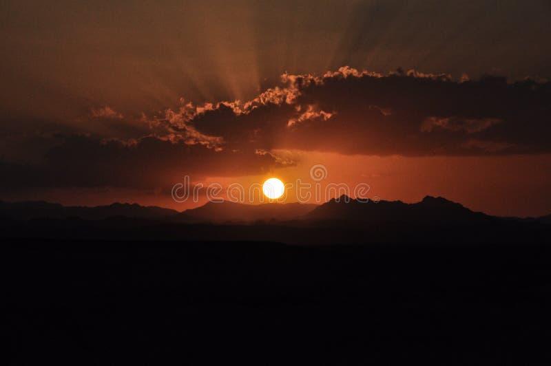 Solnedgång över bergen med solen som skiner till och med molnen royaltyfria foton