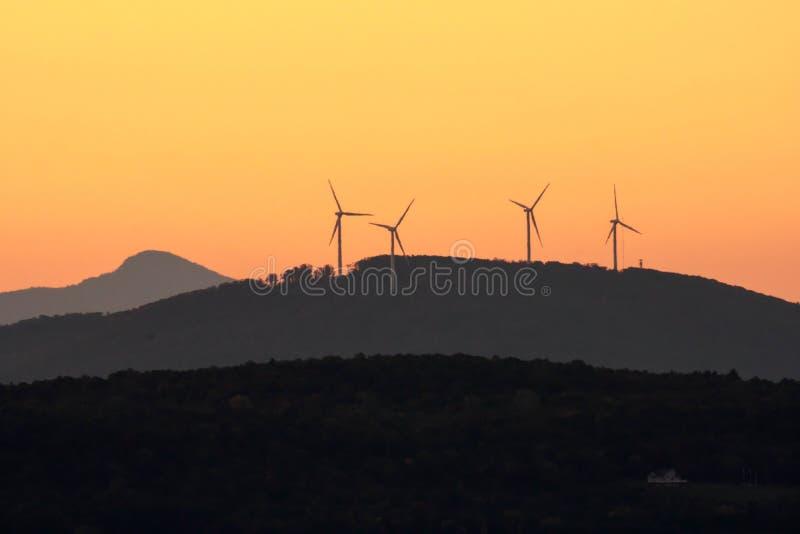 Solnedgång över bergen med vindturbiner arkivfoton