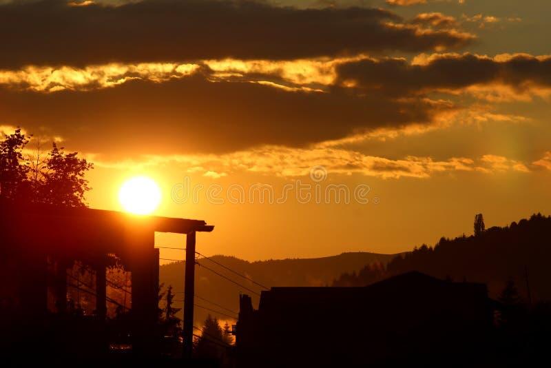 Solnedgång över berghus royaltyfria bilder