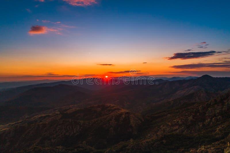 Solnedgång över bergkullar, flyg- panoramautsikt arkivbilder