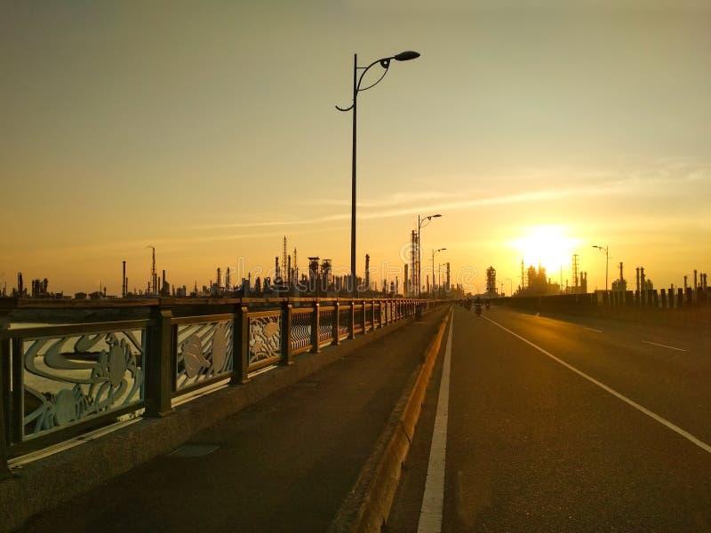 Solnedgång över bron och industriell stad med fabriker i bakgrund arkivfoto