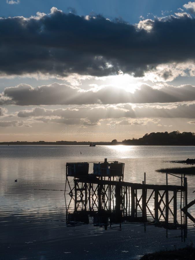 Solnedgång över bryggan för struktur för fartygpirskeppsdocka den träi flodsjön royaltyfri bild