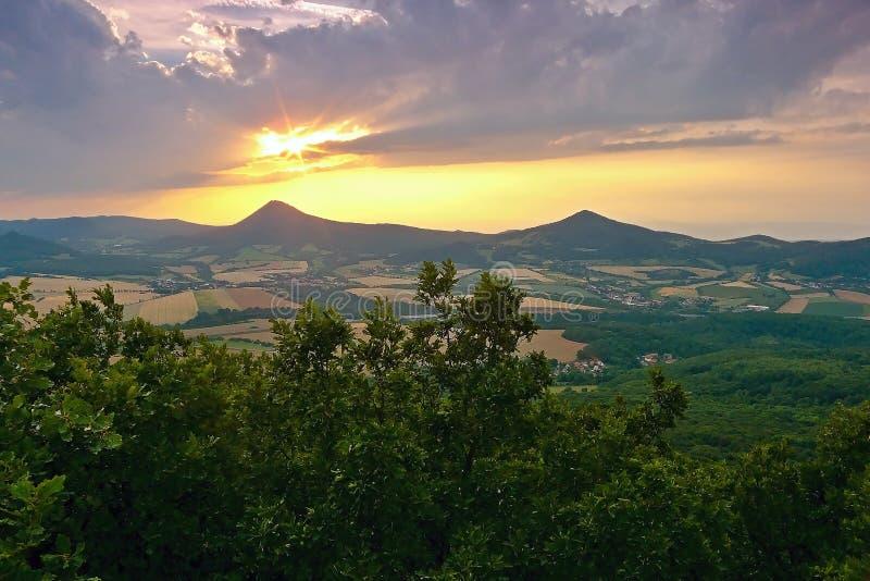 Solnedgång över den Milesovka kullen, när du beskådas från den Lovos kullen i tjeckiska centrala berg för PLOMMONER royaltyfria foton