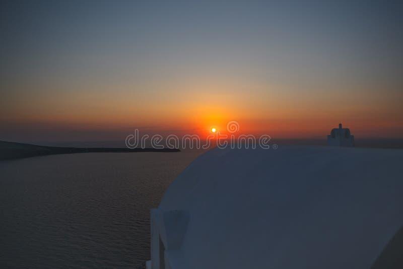Solnedgång över den Santorini ön i Grekland, lägenheter i den Oia byn på en solnedgång arkivfoton