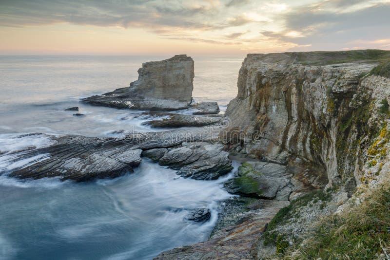 Solnedgång över den steniga kustlinjen nära panter- och Hål-I--vägg stränder royaltyfri foto