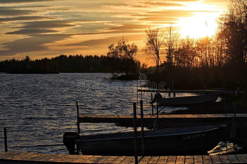 Solnedgång över den stora sjön och skeppsdockor som sticker ut in i vatten som lokaliseras i Hayward, Wisconsin royaltyfri bild