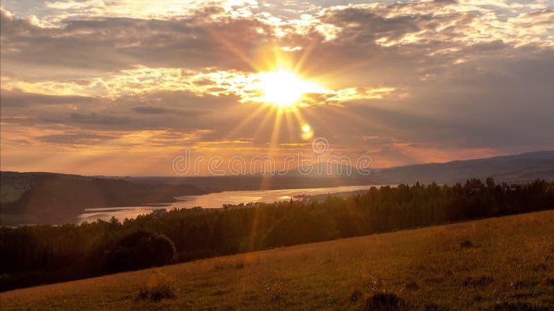 Solnedgång över en berg- och skogsjö fotografering för bildbyråer