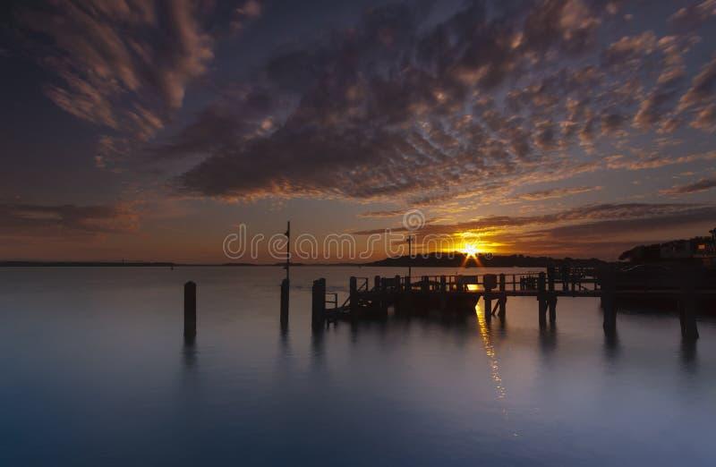 Solnedgång över en brygga nära den Brownsea ön i den Poole hamnen arkivfoto