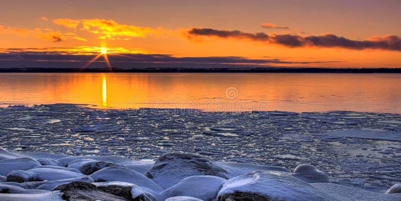 Solnedgång över en djupfryst sjö arkivfoto