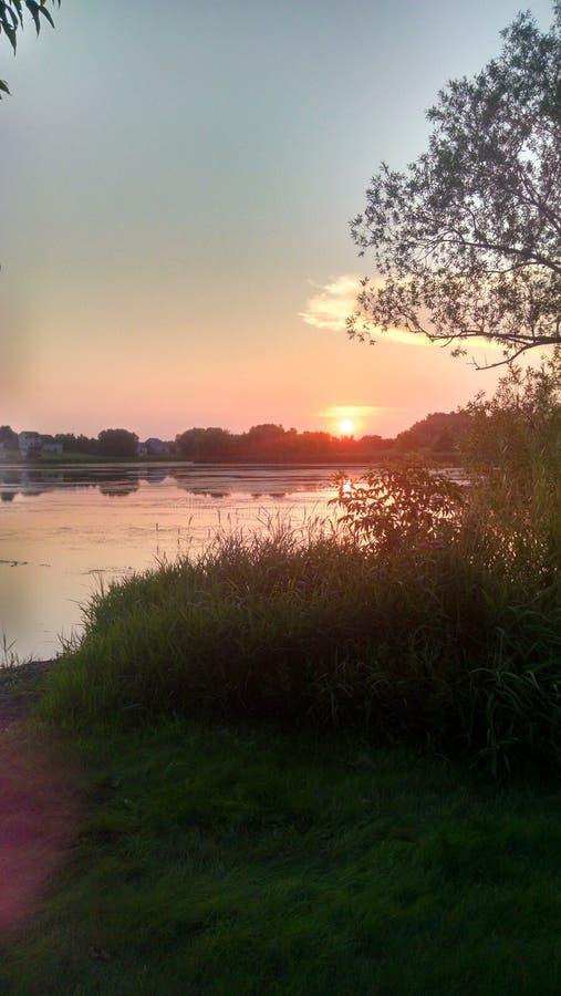 Solnedgång över en lat flod arkivfoto