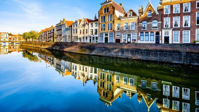 Solnedgång över en rad av hus som reflekterar på vattenyttersidan av en kanal i den historiska staden av Middelburg royaltyfri foto