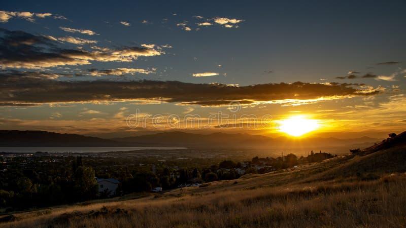 Solnedgång över en stad i en dal med berg och en stor sjö i avståndet arkivfoto