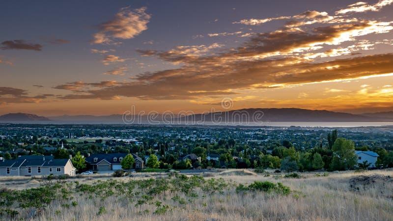 Solnedgång över en stad i en dal med berg och en stor sjö i avståndet arkivbild