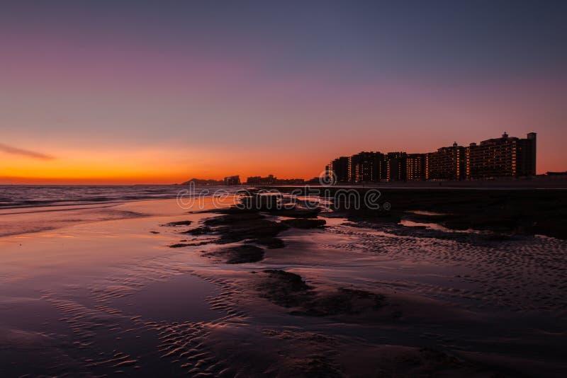 Solnedgång över en stenig strand framme hotellen arkivbilder