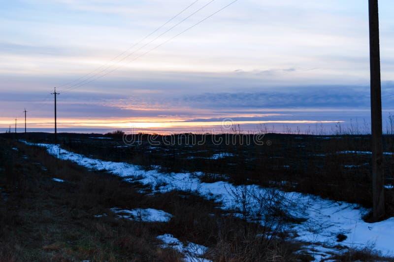 Solnedgång över fältet, i några ställen som täckas med snö royaltyfria bilder