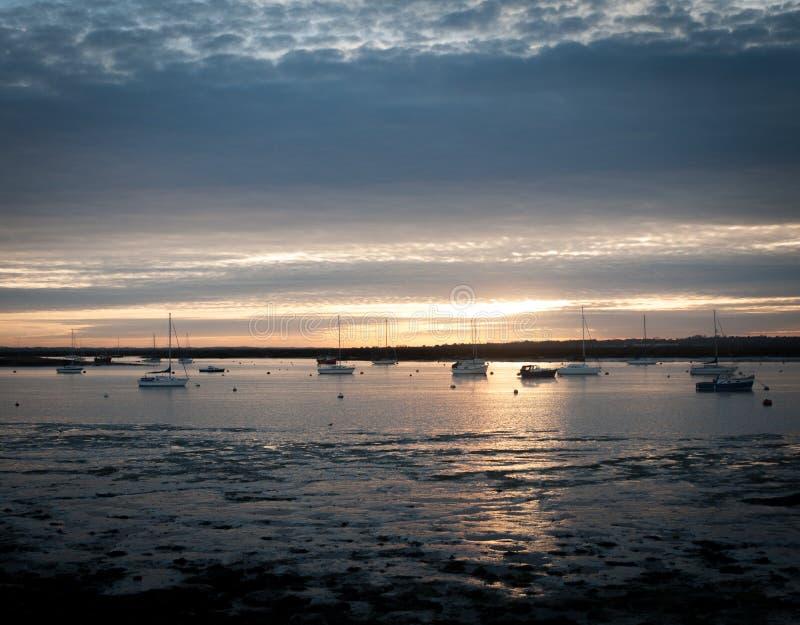 Solnedgång över för essex för mersea för flodbred flodmynning västra fartyg för kust sjösida arkivbild