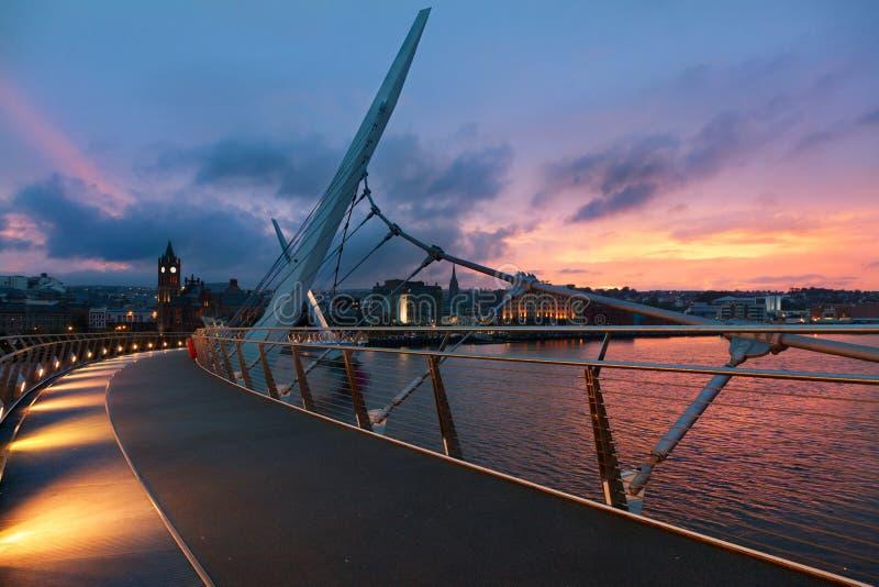 Solnedgång över fredbron av Derry som är nordlig - Irland royaltyfria bilder