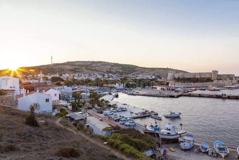 Solnedgång över gammal stad, port och catle av den Bozcaada Tenedos ön vid det Aegean havet fotografering för bildbyråer