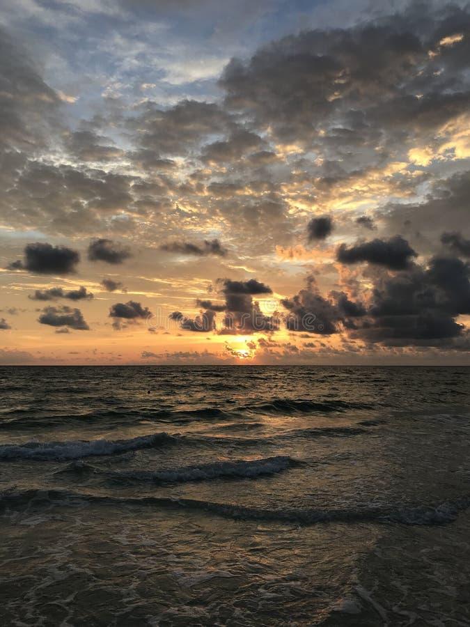 Solnedgång över havet med att kontrastera moln royaltyfri fotografi