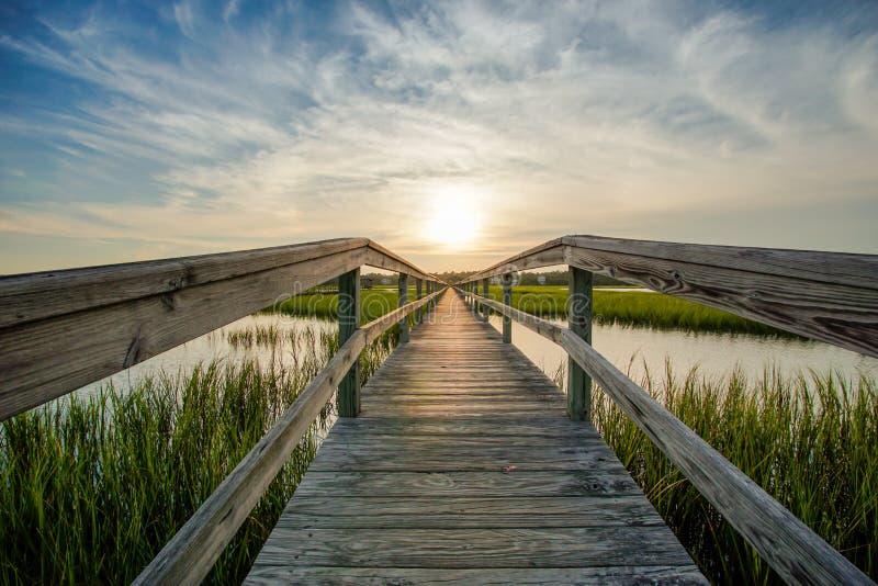 Solnedgång över kust- vatten med en mycket lång trästrandpromenad royaltyfri fotografi