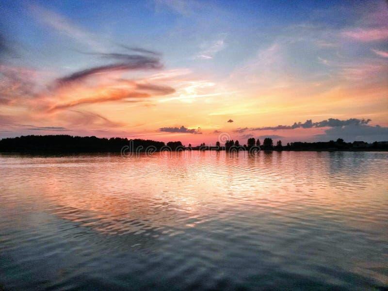 Solnedgång över laken arkivfoto