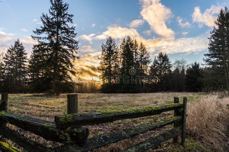 Solnedgång över lantligt lantgårdland royaltyfri bild