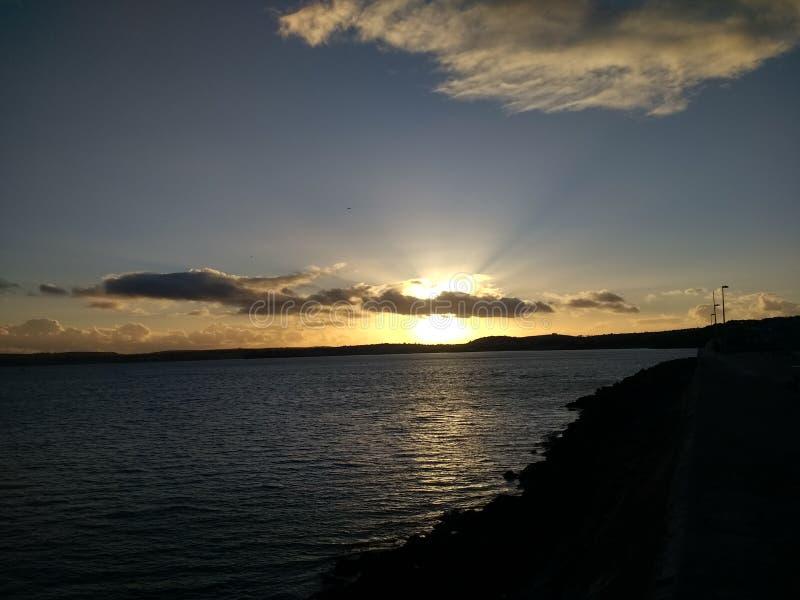 Solnedgång över molnig himmel royaltyfri bild