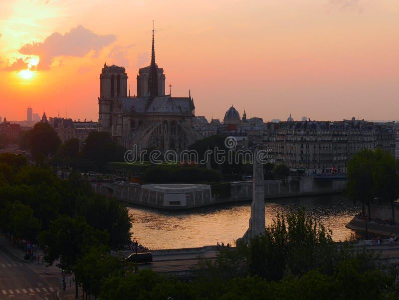 Solnedgång över Notre Dame de Paris och Seinet River royaltyfri foto