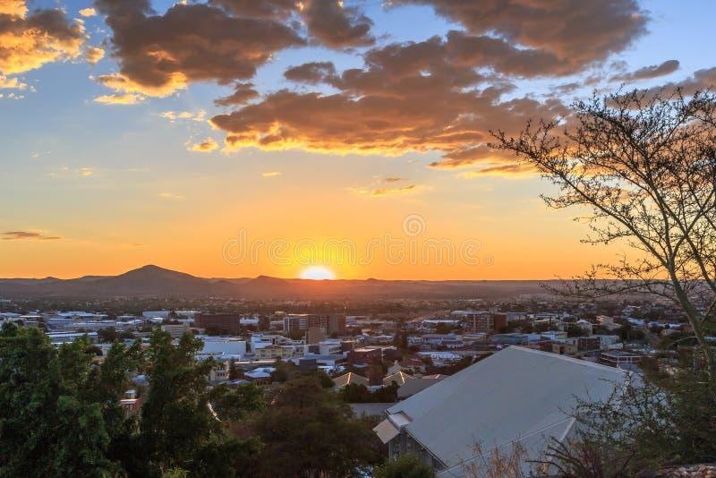 Solnedgång över område Windhoek för central affär med solen och moun royaltyfri fotografi