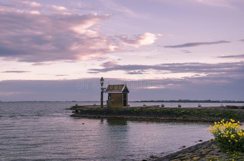 Solnedgång över pier, Volendam, Nederländerna royaltyfri foto