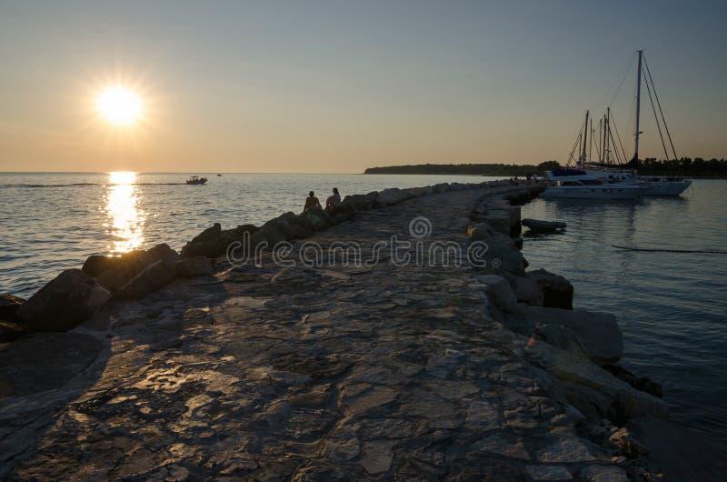 Solnedgång över pir och hamn i Novigrad, Kroatien, Europa arkivbild