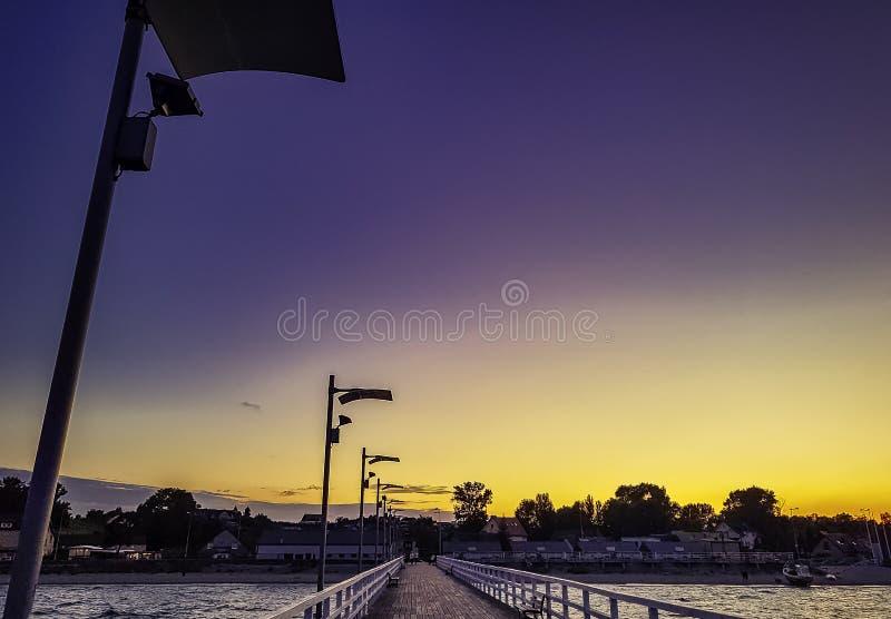 Solnedgång över pir och polsk kust i Rewa, Pomerania, Polen royaltyfri foto