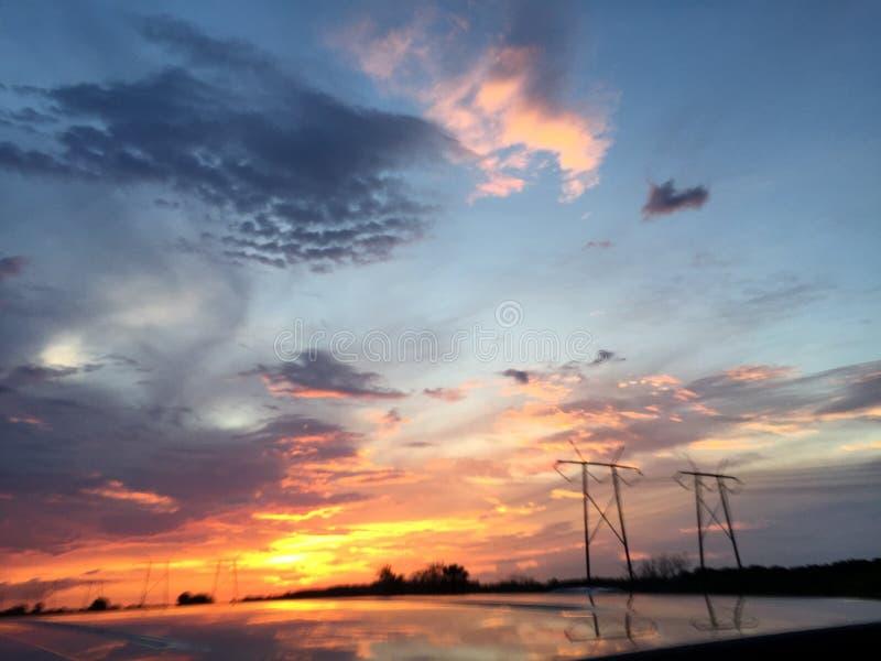 Solnedgång över powerlinesna royaltyfri foto