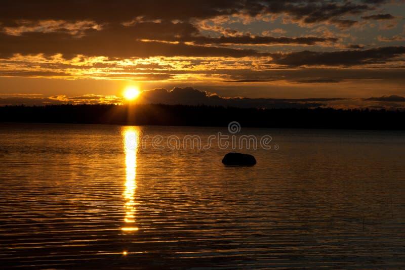 Solnedgång över sjön. arkivfoton