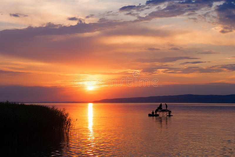 Solnedgång över sjön Balaton med sportfiskare`-konturer i Ungern arkivfoton