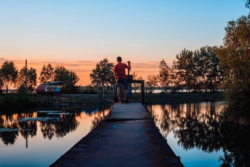 Solnedgång över sjön och pojken royaltyfri foto