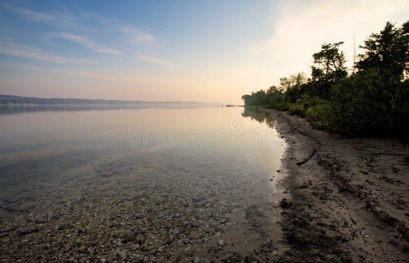 Solnedgång över sjöshoreline arkivfoto