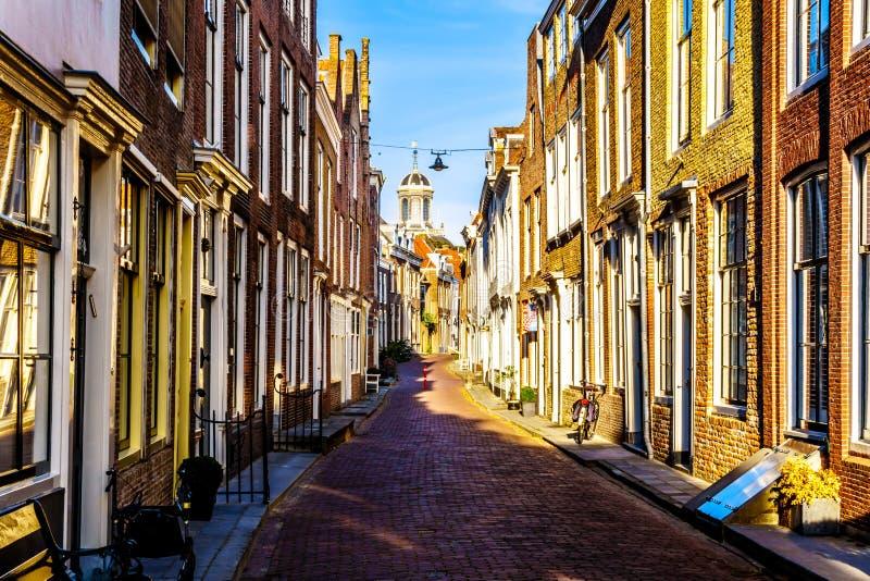 Solnedgång över smala gator i den historiska staden av Middelburg i det Zeeland landskapet, Nederländerna royaltyfri fotografi