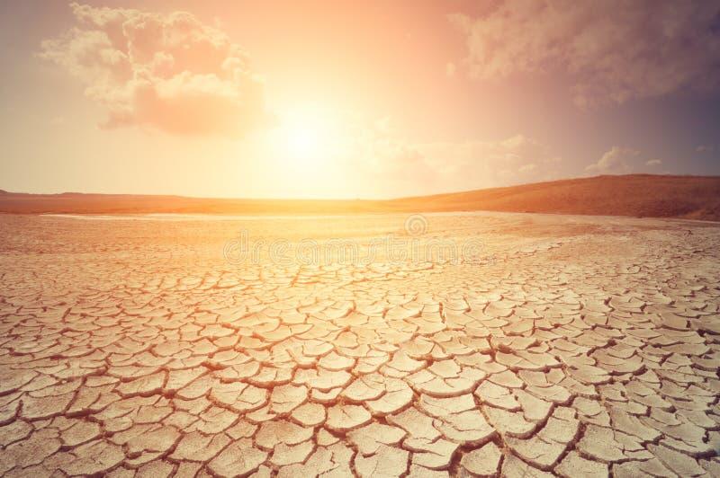 Solnedgång över sprucken jord royaltyfri fotografi