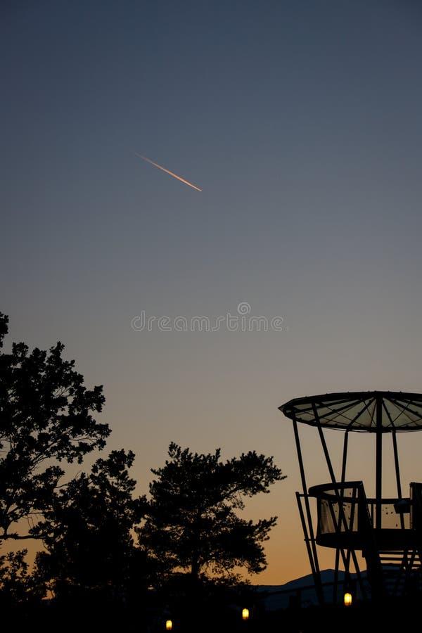 Solnedgång över staden med abservationdäcket och trädkonturn fotografering för bildbyråer