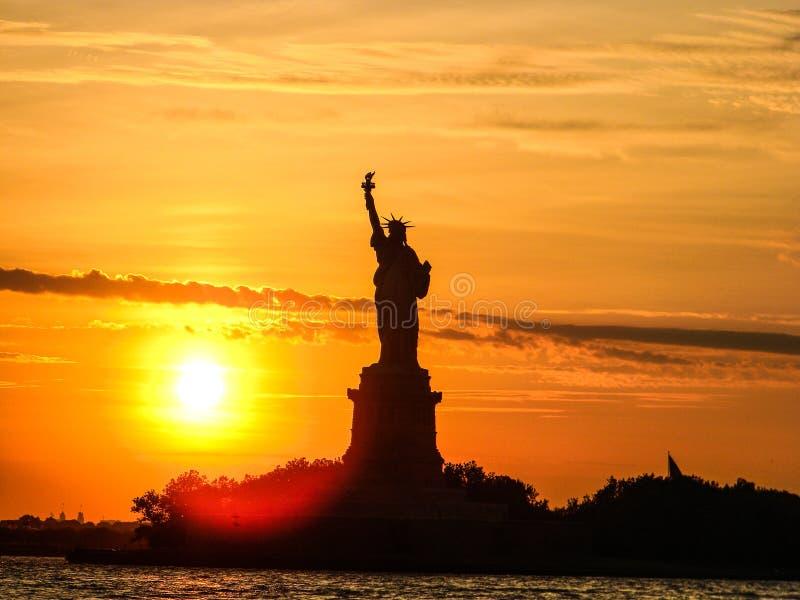Solnedgång över statyn av frihet arkivbild
