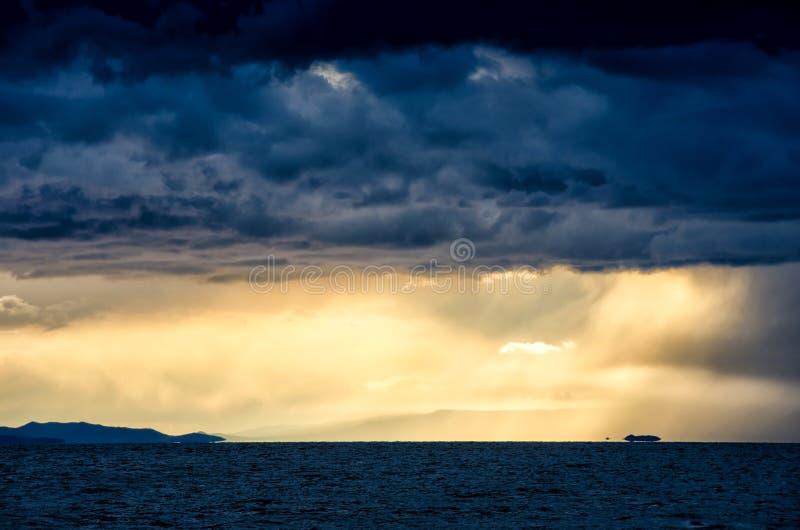 Solnedgång över stormiga moln över mörkret och att hägra för vatten det reflekterande lynnig dramatisk himmel arkivfoton