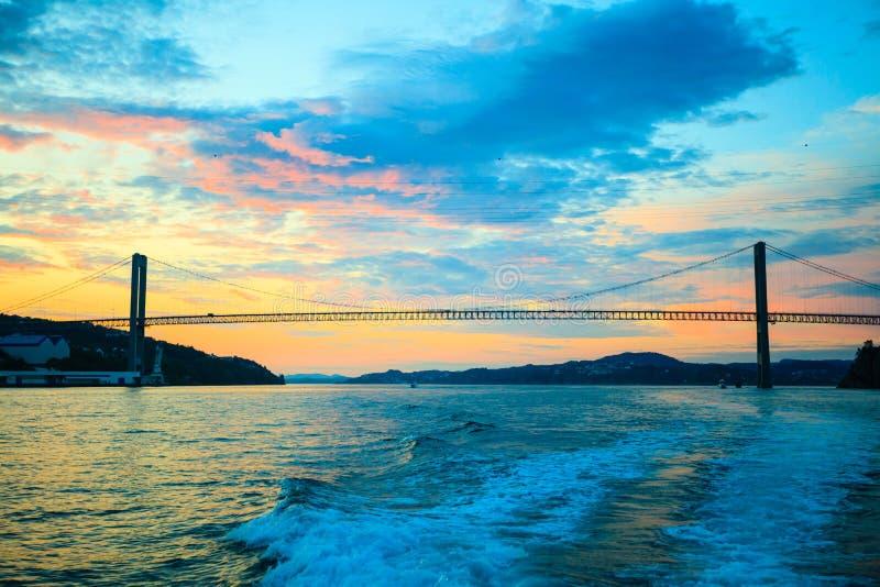 Solnedgång över upphängningbron i Bergen, Norge arkivfoton