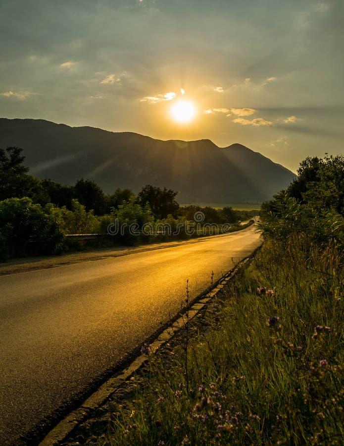 Solnedgång över vägen nära bergen arkivbilder