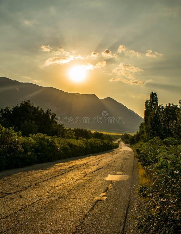 Solnedgång över vägen nära bergen royaltyfria foton